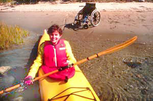 Lady in kayack on the water in the forground smiling with her wheelchair on beach behind her in background.